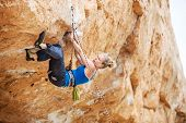 stock photo of struggle  - Young female rock climber struggling to make next movement up - JPG