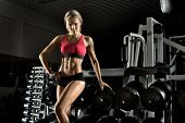 stock photo of execution  - beautiful girl bodybuilder execute exercise with weight - JPG