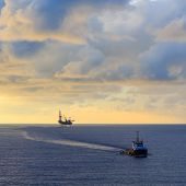 foto of offshore  - Offshore jack up drilling rig and supply boat in the middle of the ocean during sunset time - JPG