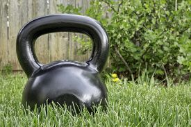 stock photo of heavy  - heavy iron black kettlebell on green grass in backyard  - JPG