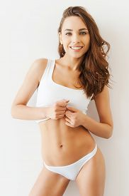 pic of panties  - Attractive young woman in white tank top and panties posing while standing against white background - JPG