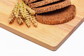 pic of malt  - Slices of rye malt bread and wheat ears on the chopping board - JPG