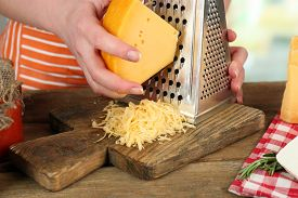 picture of grating  - Closeup of female hands grating cheese - JPG