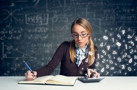 foto of schoolgirl  - Schoolgirl doing  mathematics with math formulas  - JPG