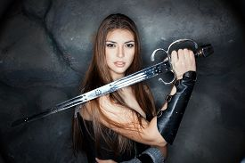 stock photo of sword  - Beautiful girl holding a steel sword in his hand - JPG