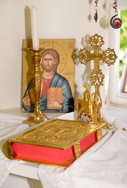 stock photo of baptism  - Interior of a very small greek chapel with holy bible golden cross and oil for baptism - JPG