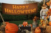 image of happy halloween  - autumn scene with pumpkins scarecrow and banner that says  - JPG