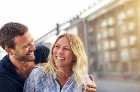 stock photo of vivacious  - Happy vivacious romantic young couple enjoying a good joke hugging and laughing merrily as they stand outdoors on am urban residential street