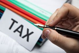 foto of scat  - pen in hand and metaphor for the payment of taxes - JPG