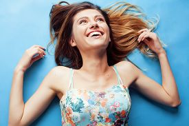 stock photo of fool  - young pretty woman fooling around on blue background close up smiling - JPG