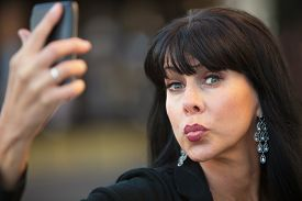 stock photo of snob  - Attractive woman taking silly selfie with black cell phone - JPG