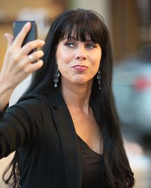 picture of snob  - Attractive woman taking selfie with black cell phone - JPG