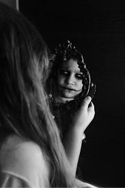 picture of horrifying  - a girl staring at the mirror but her reflection is horrifying.