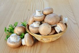 image of crimini mushroom  - Cremini mushrooms brown cap in a basket over wooden table - JPG