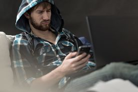 picture of irritated  - Irritated guy reading a text message from his girlfriend - JPG