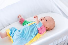 foto of bassinet  - Newborn baby boy playing in bed on a sunny morning - JPG