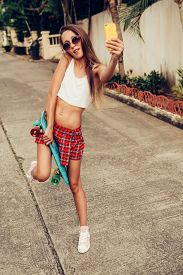 image of mini-skirt  - Sexy beautiful woman in a red tartan mini skirt with skateboard taking a selfie self portrait at the camera on her smartphone digital camera - JPG