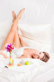 image of laying-in-bed  - Pretty woman looking at camera while laying in bed - JPG