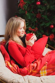 foto of sad christmas  - Sad woman sitting alone with a cup of tea nearby Christmas tree - JPG