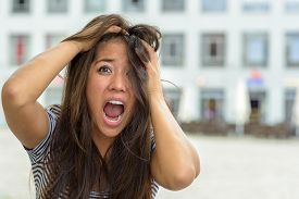 image of horror  - Woman yelling in horror and fear while tearing at her hair with a look of panic outdoors on an urban street close up of her face - JPG