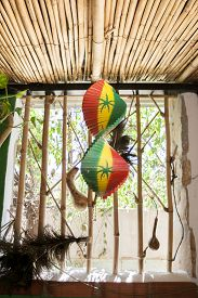 picture of reggae  - Hanging wooden spiral decorative craft with reggae color over open window of a tropical hut - JPG