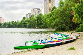 picture of pedal  - Pedal boats parked near the sandy shore against the backdrop of the river trees and city building cloudy day - JPG