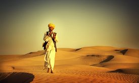 stock photo of wind instrument  - Indigenous Indian Man Playing Wind Pipe In A Desert Concept - JPG
