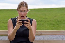 picture of shock awe  - Young woman reacting in shock to an sms of text message on her mobile phone looking at the screen in wide eyed horror as she sits on a park bench outdoors - JPG