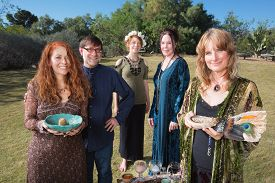 foto of wicca  - Five smiling Wicca practitioners standing outdoors with smudge stick - JPG