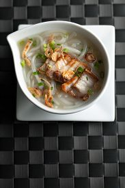 stock photo of crispy rice  - Close up top down view of Thai style crispy pork rice noodle soup in a bowl - JPG