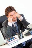 Homem de negócios entediados sentado no escritório de turismo e manter cabeça em mãos