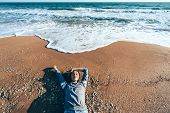 Young girl in sweater relaxing on sand by sea wave. Chilling on the coast and breathing fresh breeze poster
