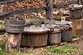 foto of split rail fence  - collection of weathered wooden buckets of various sizes against split - JPG