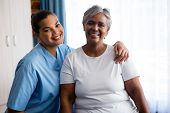 Portrait of young nurse with senior patient in nursing home poster