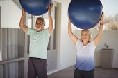 Senior couple lifting exercise ball while exercising poster