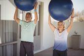 Senior couple lifting exercise ball while exercising poster