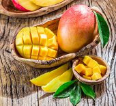 Mango fruit and mango cubes on the wooden table. poster