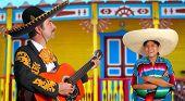 Mexican mariachi charro man and poncho Mexico girl colorful facade houses