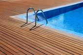blue swimming pool with teak wood flooring stripes summer vacation