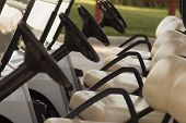 stock photo of foursome  - golf carts lined up - JPG
