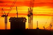 stock photo of construction crane  - cranes on high rise construction site at sunset - JPG