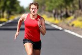 Running sport man. Fit muscular young male runner sprinting at great speed outdoors on road.