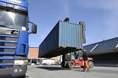 forklift moving container from truck in commercial container-port