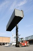 forklift truck lifting large container high in the air