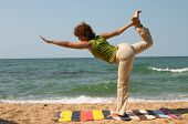 picture of natarajasana  - girl doing Natarajasana yoga pose on the seaside - JPG