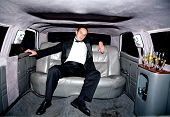 picture of luxury cars  - guy inside a limousine all alone with some champagne - JPG