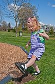 stock photo of mary jane  - This Caucasian 3 year old toddler girl is stomping dirt in her black Mary Jane shoes outdoors in a park - JPG