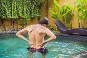Mens Back Hurts Against The Backdrop Of The Pool. Pool Helps With Back Pain poster