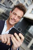 Young business man navigating in urban city with smartphone