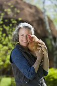 stock photo of geodesic  - Woman holding chicken outside her geodesic home - JPG